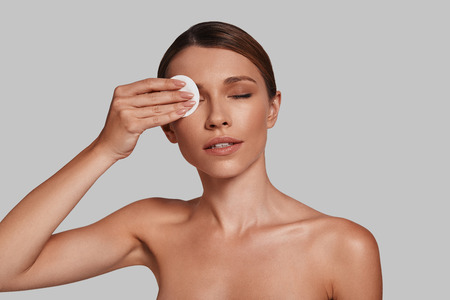 Beauty treatment. Attractive young woman applying cotton pad and smiling while standing against grey background Imagens