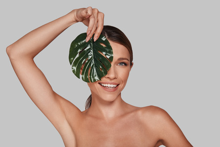 Happiness highlights her beauty. Attractive young woman looking at camera and covering face with leaf while standing against grey background