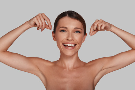 Perfect skin. Attractive young woman looking at camera and smiling while standing against grey background Imagens - 104361456