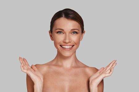 Sensitive care for a luminous skin. Attractive young woman looking at camera and smiling while standing against grey background Imagens