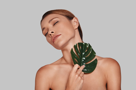 Time for yourself. Attractive young woman keeping eyes closed and covering with leaf while standing against grey background Imagens
