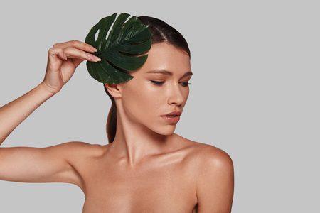 Supremely sensual. Attractive young woman looking away and covering with leaf while standing against grey background