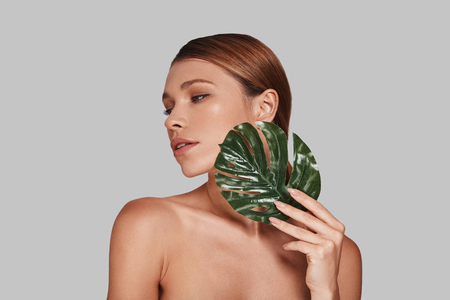 So soft... Attractive young woman looking away and covering with leaf while standing against grey background
