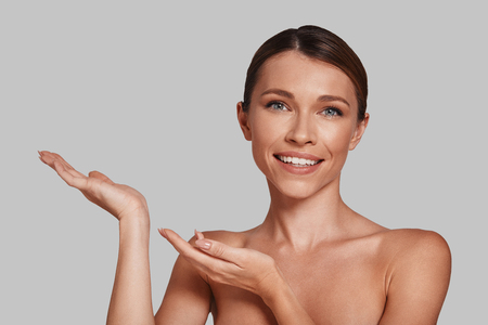 Pointing copy space. Attractive young woman pointing copy space and smiling while standing against grey background