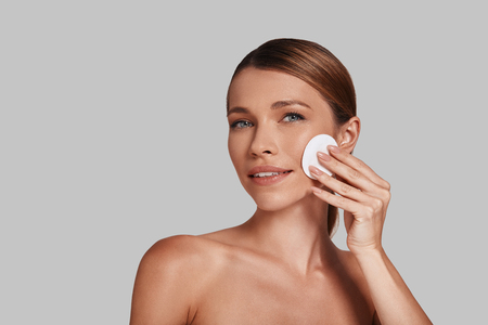 Taking good care of her skin. Attractive young woman applying cotton pad and smiling while standing against grey background Imagens
