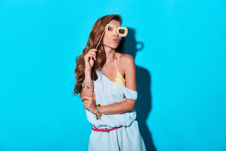 In a mood for a big holiday. Attractive young woman making a face and holding prop while standing against blue background