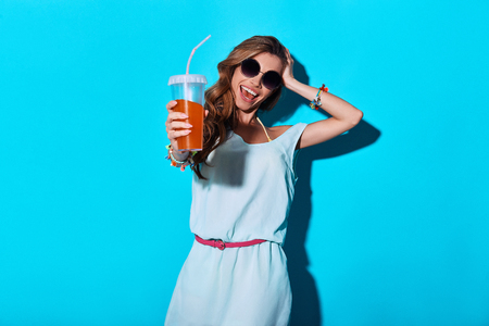 To the summer! Attractive young woman smiling and toasting you while standing against blue background Foto de archivo - 105450482