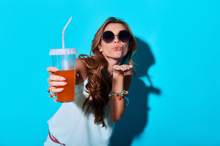 Carefree and happy.  Attractive young woman blowing a kiss and toasting you while standing against blue background Foto de archivo - 105450436