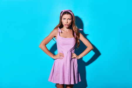 a bad mood. Angry young woman looking at camera and keeping hands on hips while standing against blue background