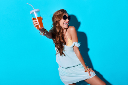 Party girl. Attractive young woman smiling and toasting you while standing against blue background Foto de archivo - 105448508