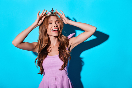 So good to be the queen! Attractive young woman adjusting her tiara and smiling while standing against blue background 스톡 콘텐츠