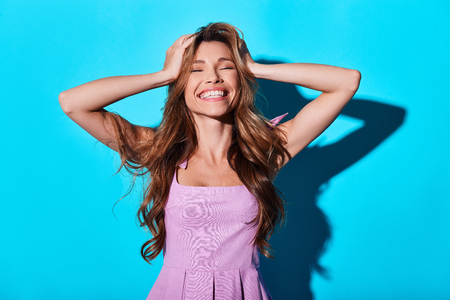 Just happy. Beautiful young woman smiling and keeping head in hands while standing against blue background Stock fotó
