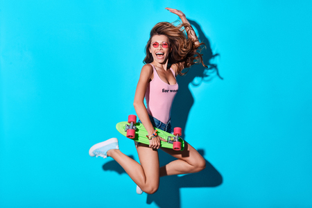Mid-air beauty. Attractive young woman smiling and looking at camera while jumping against blue background