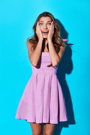 No way! Surprised young woman making a face and looking at camera while standing against blue background
