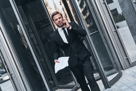 Successful businessman. Serious young man in full suit talking on the phone while walking outdoors