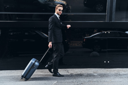 Confident businessman. Full length of young man in full suit pulling luggage and checking the time while walking outdoors