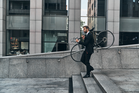 Avoiding traffic. Full length of young man in full suit carrying his bicycle while walking outdoors Stock Photo