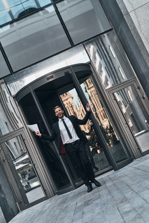 Success! Full length handsome young man in full suit gesturing and smiling while standing outdoors Stock Photo