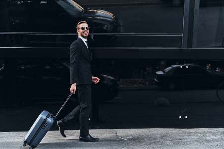 Young and successful. Full length of young man in full suit pulling luggage and smiling while walking outdoors