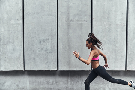 Ready to break any record. Modern young woman in sports clothing jumping while exercising outdoors Stock fotó