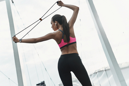 Determined to win. Rear view of modern young woman in sports clothing exercising using resistance band while standing outdoors