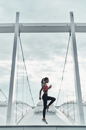 Cardiovascular exercise. Full length of modern young woman in sports clothing jumping while exercising outdoors
