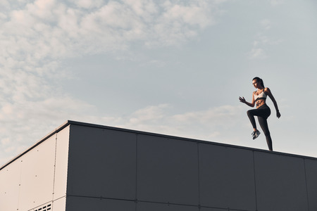 Fitness is the way of life. Full length of modern young woman in sports clothing jumping while exercising time on the roof outdoors