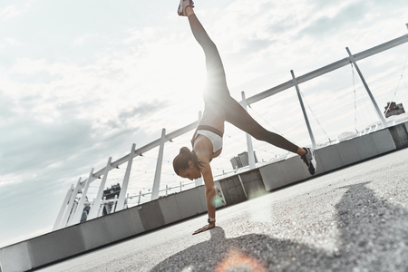World upside down. Full length of modern young woman in sports clothing doing handstand while exercising outdoors Stock Photo