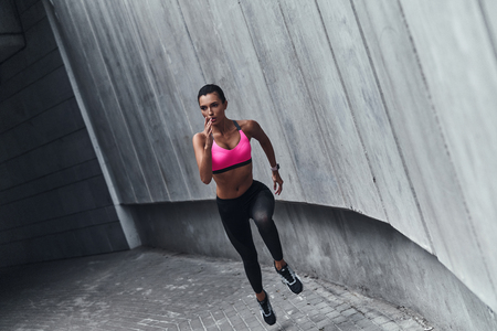 Giving all her best. Full length of modern young woman in sports clothing jumping while exercising outdoors Stock fotó