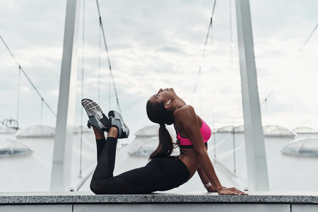 Reaching for her fitness goals. Modern young woman in sports clothing stretching while warming up outdoors Banco de Imagens - 105446495