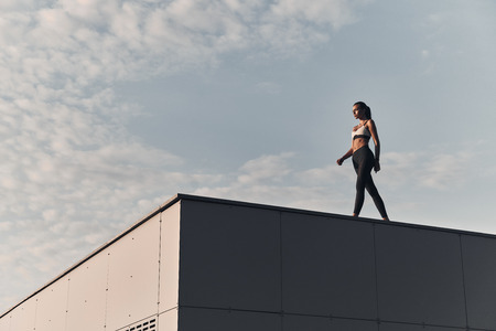 She is in a good shape. Full length of modern young woman in sports clothing walking while spending time on the roof outdoors Stock Photo