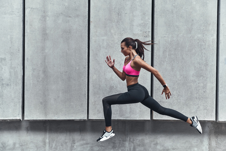 Long jump. Modern young woman in sports clothing jumping while exercising outdoors Stock fotó