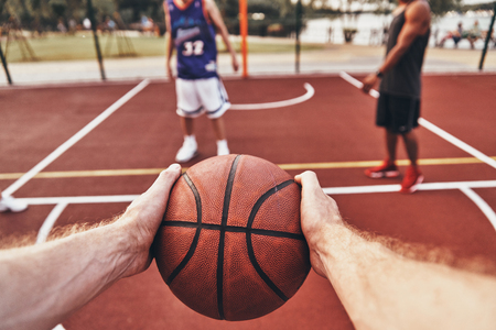 Keep playing. Close up of man holding ball while playing basketball with friends outdoors Stock Photo