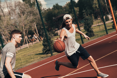 Pushing hard. Two young men in sports clothing playing basketball while spending time outdoors