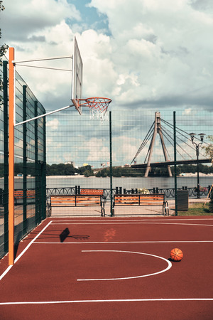 Waiting for players. Shot of basketball ball lying on the empty basketball playground outdoors