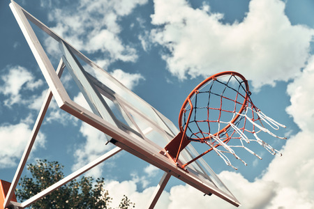 Let the game begin. Shot of basketball hoop with sky in the background outdoors Фото со стока