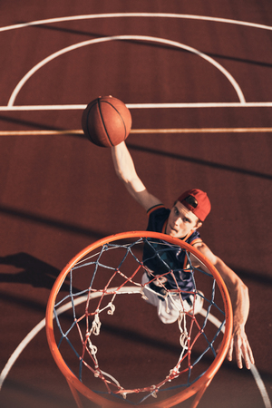 Best basketball player. Top view of young man in sports clothing scoring a slam dunk while playing basketball outdoors Stock Photo