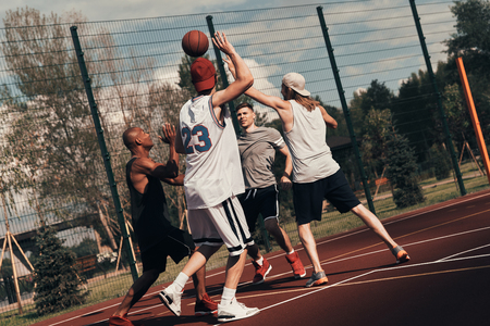 Training to become the best. Group of young men in sports clothing playing basketball while spending time outdoors
