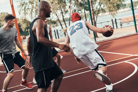 Quick as a narrow. Group of young men in sports clothing playing basketball while spending time outdoors