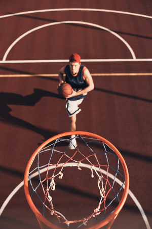 Always aimed to win. Top view of young man in sports clothing preparing to score a slam dunk while playing basketball outdoors
