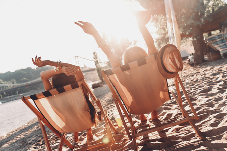 Summer day. Rear view of two women sunbathing while resting in outdoor chairs on the beach