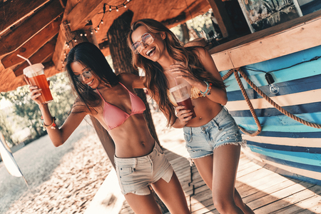 No rules for them. Two attractive young women smiling and enjoying cocktails while dancing near the bar counter