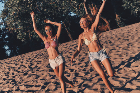 No cares. Two attractive young women in shorts and swimwear smiling and gesturing while running on the beach Stock Photo