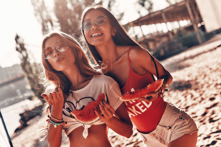 Lazy hot day. Two attractive young women smiling and eating watermelon while standing on the beach