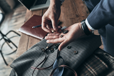 Searching for right decision. Close up top view of fashion designer choosing buttons while working in clothing design studio Stock Photo