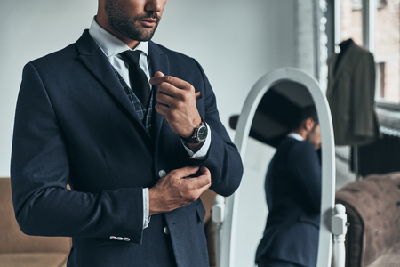 Perfect style. Close up of young man in full suit adjusting sleeve while standing indoors