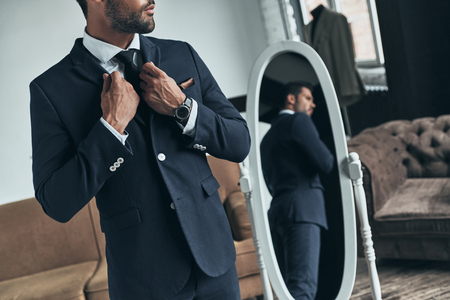 Everything must be perfect. Close up of young man in full suit adjusting jacket while standing indoors
