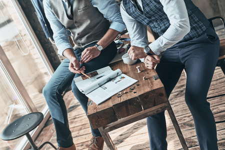 Going over details. Close up top view of two men choosing design while spending time in the workshop Stock Photo