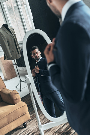 Looking just perfect. Reflection of handsome young man in full suit adjusting his jacket while standing in front of the mirror indoors Banco de Imagens