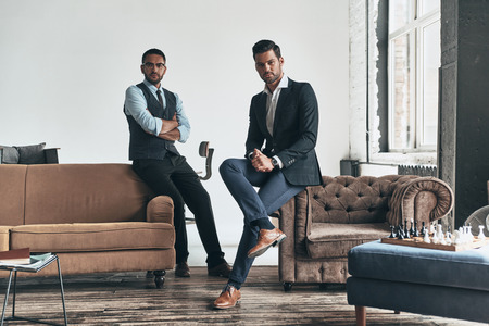 Men with a great style. Two young handsome men in suits looking at camera while resting indoors